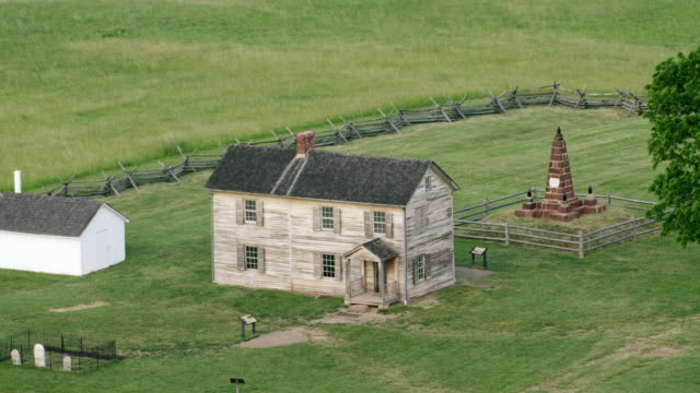 WS AERIAL POV House with memorial structure on grassy landscape at Manassas National Battlefield Park / Manassas, Virginia, United States