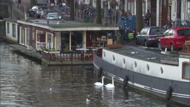 vídeos de stock e filmes b-roll de a houseboat and other boats dock along a busy waterfront road in amsterdam. - barco casa