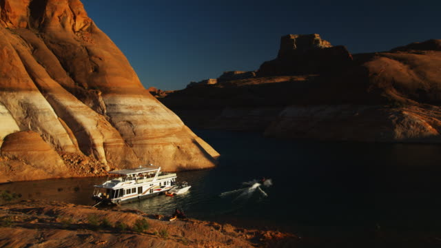 vídeos de stock e filmes b-roll de houseboat on a desert lake - lago powell
