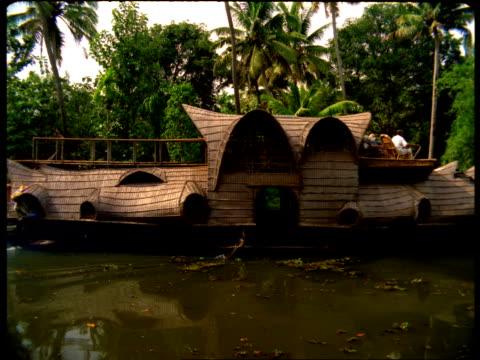 vídeos de stock e filmes b-roll de a houseboat passes by on a river in india. - barco casa