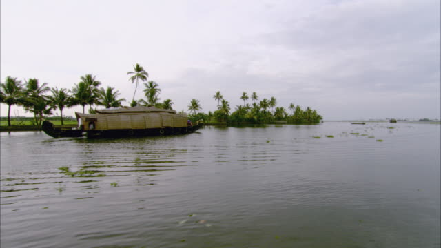 vídeos de stock e filmes b-roll de ws ts pan houseboat traveling on river along island coast / india - barco casa