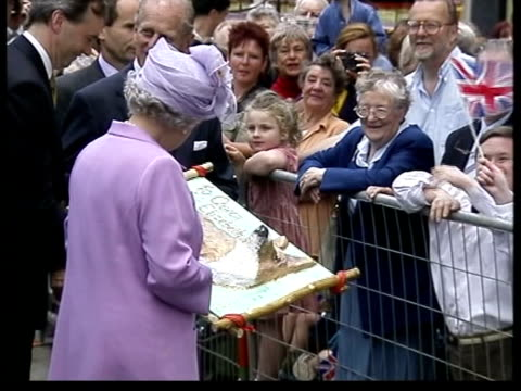 household accounts revealed; pool england: northamptonshire: kettering ext queen elizabeth ii receiving papier mache model of corgi from man in... - papier 個影片檔及 b 捲影像