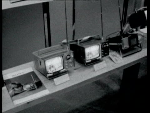 vidéos et rushes de household appliances pots and pans electronic blenders on display / woman looking at washing machine / men looking at television sets and looking... - 1964