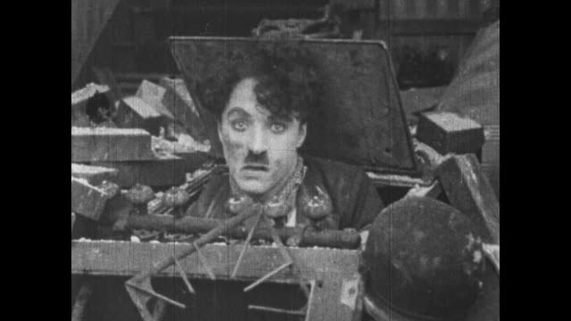 vídeos de stock, filmes e b-roll de 1915 household members poke their heads up through rubble of explosion as charlie chaplin pops head out of exploded stove - charlie chaplin