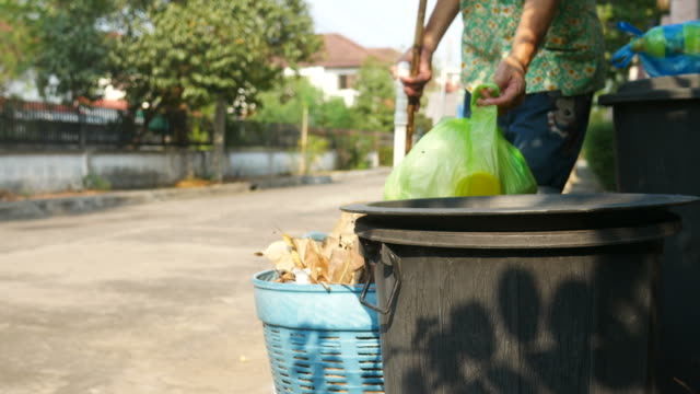 vidéos et rushes de femme de ménage déposer les ordures dans le bac noir - trottoir