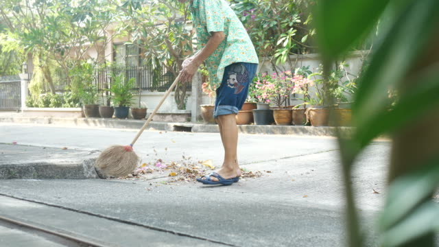 housekeeper sweeping foliage - sweeping stock videos & royalty-free footage