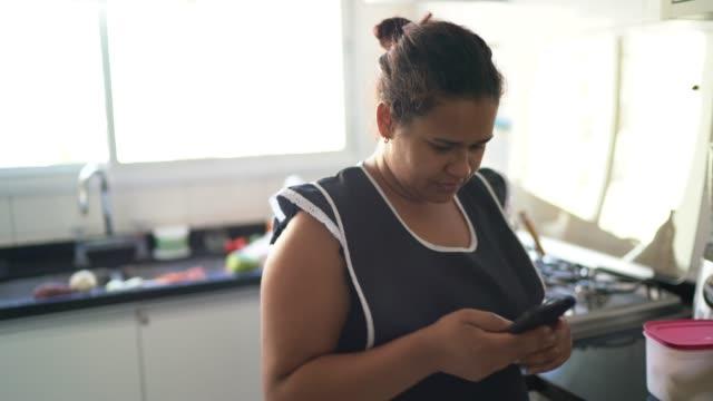 vidéos et rushes de femme de ménage marchant et utilisant le téléphone portable à la maison - mobilité