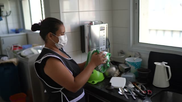 housekeeper washing the dishes wearing protective mask - mid adult women stock videos & royalty-free footage