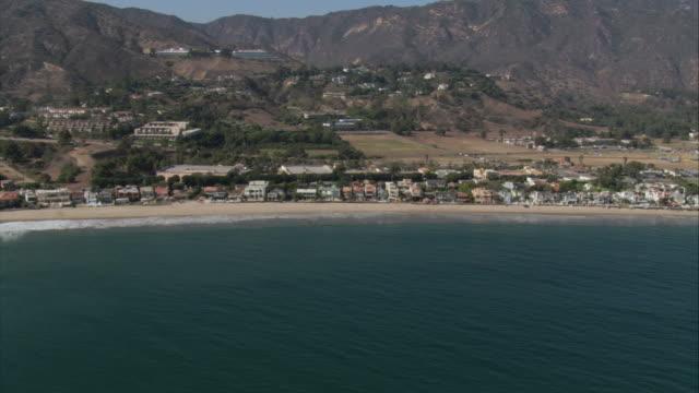 vidéos et rushes de aerial houses along the pacific coast, near base of mountain range / malibu, california, united states - malibu