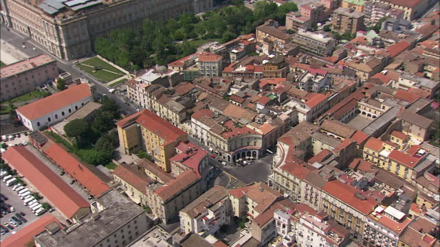 houses and buildings surround a small plaza in the city of caserta in southern italy. - palace video stock e b–roll