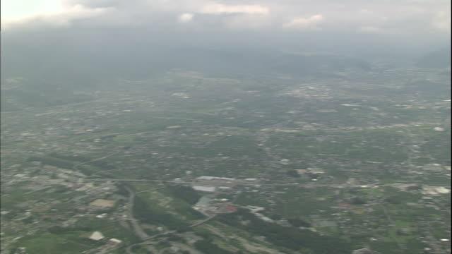 houses and fields of yamanashi cover the kofu basin in japan. - 山梨県点の映像素材/bロール