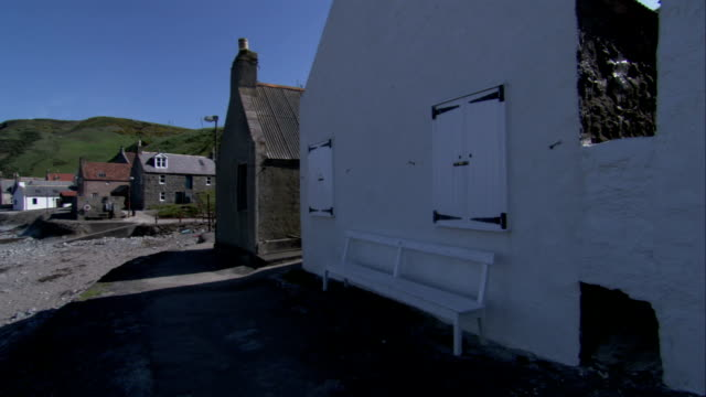 houses cast shadows on the rocky shores of crovie scotland. available in hd. - クロヴィー点の映像素材/bロール