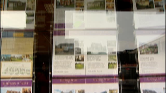 houses for sale in estate agents window city building and sign advertising train services from corby to london price of house for sale in estate... - for sale englischer satz stock-videos und b-roll-filmmaterial