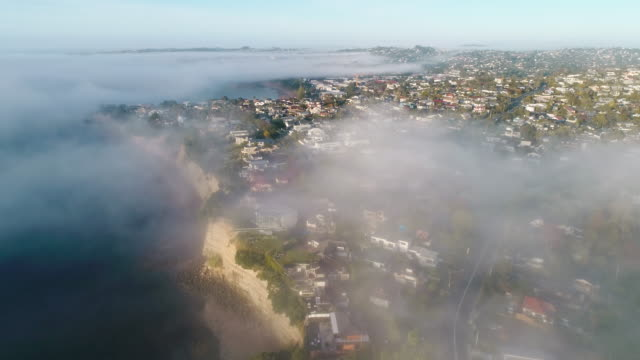 houses next to beach covered with fog. - auckland stock videos & royalty-free footage