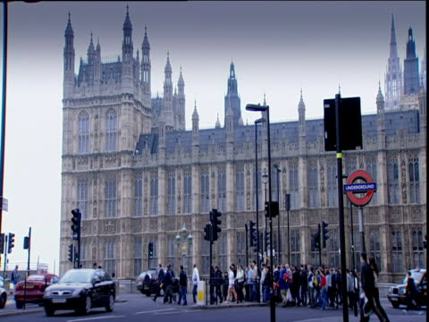 stockvideo's en b-roll-footage met houses of parliament against grey skies with traffic and pedestrians passing london underground sign in foreground - jaar 2000 stijl