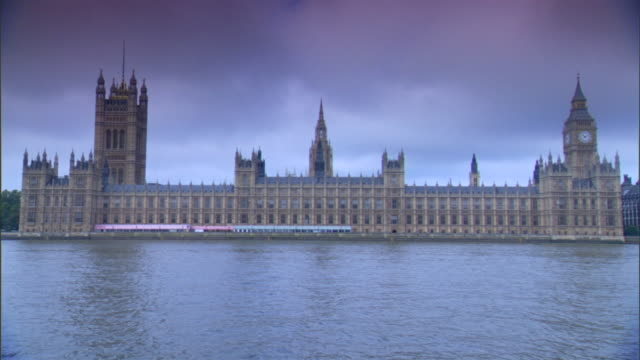 WS Houses of Parliament on north bank of River Thames w/ Victoria Tower Clock Tower housing Great Bell Big Ben pink clouds No people