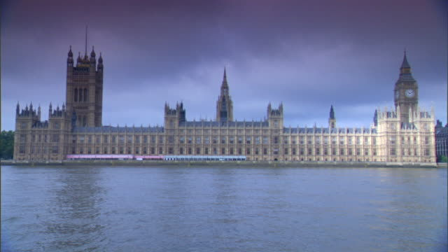 PARLIAMENT CLOUDY HD TU WS Houses of Parliament on north bank of River Thames w/ Victoria Tower Clock Tower housing Great Bell Big Ben sunlight...