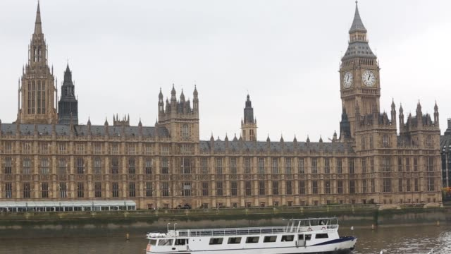 stockvideo's en b-roll-footage met houses of parliament reflected in a puddle on a gloomy day in westminster, london on tuesday, october 14 a boat floats past the terrace restaurant,... - alle vlaggen van europa