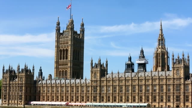 houses of parliament with british flag raised - bandiera del regno unito video stock e b–roll