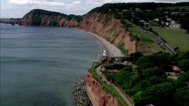 houses on a shoreline cliff overlook the sea. available in hd. - cliff stock videos & royalty-free footage
