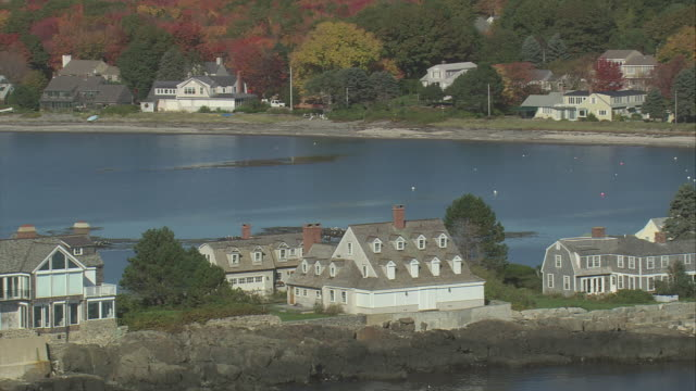 aerial houses on lords point, with more houses and intense fall colors on the shore beyond / kennebunkport, maine, united states - village stock videos & royalty-free footage