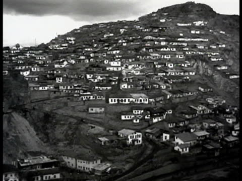 Houses on mountain side hill WS Road on hill gravel Turkish people walking MS House on hillside people children