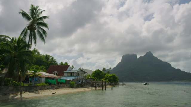 houses on tropical beach near mountain / bora bora, french polynesia - フランス領ポリネシア点の映像素材/bロール