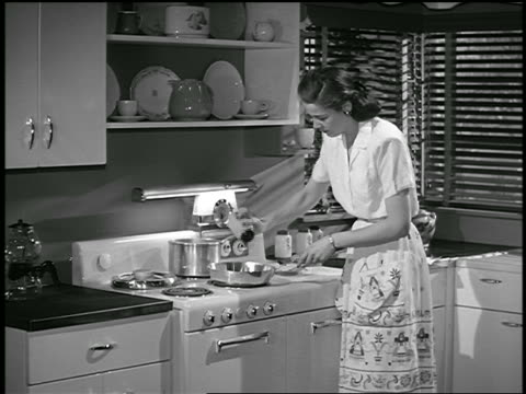 b/w 1948 housewife at stove cooking / industrial - hausfrau stock-videos und b-roll-filmmaterial