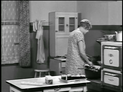 vídeos de stock, filmes e b-roll de b/w 1929 housewife cooking at stove in kitchen / newsreel - 1920 1929
