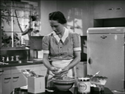 stockvideo's en b-roll-footage met b/w 1938 housewife cooking in kitchen breaking eggs into bowl / educational / industrial - prelinger archief