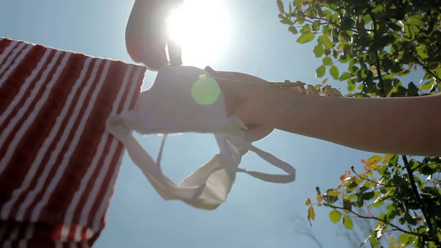 stockvideo's en b-roll-footage met housewife drying laundry outdoors to save energy - wasknijper
