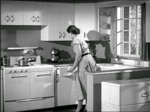 b/w 1950 pan housewife entering kitchen / puts on apron + stirs pot on stove / opens refrigerator - hausfrau stock-videos und b-roll-filmmaterial