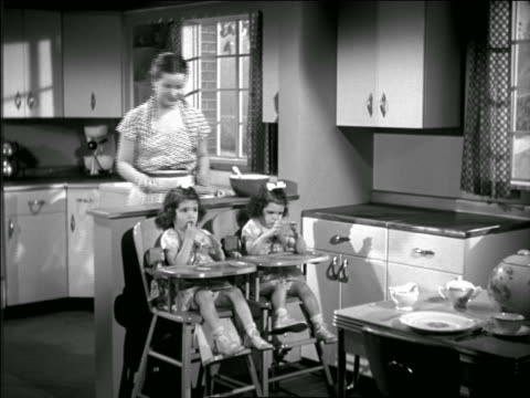 b/w 1950 housewife feeding twin girls sitting in high chairs in kitchen - stay at home mother stock videos & royalty-free footage