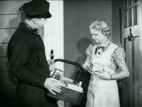 b/w 1938 housewife greeting door-to-door salesman at door + taking items from basket / industrial - door to door salesperson stock videos & royalty-free footage