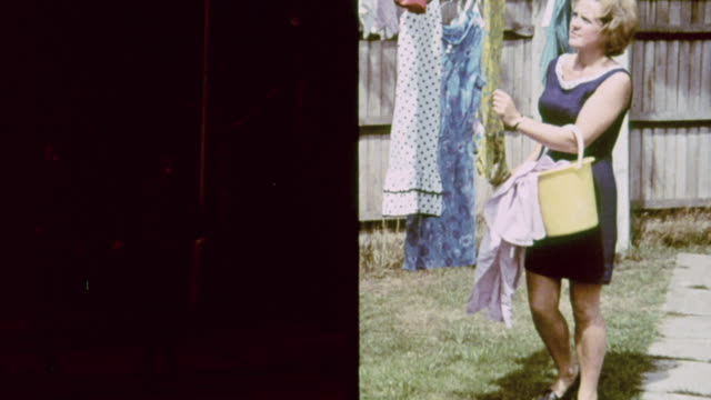 vidéos et rushes de montage housewife hanging laundry on the clothesline as kids play outside and car drives on the highway / united kingdom - lessive corvée domestique
