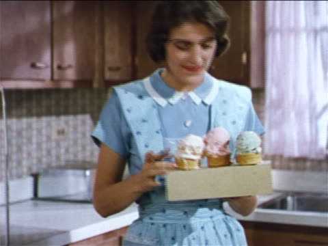 1962 housewife holding box of ice cream cones as children clamor around her / industrial - ice cream cone stock videos & royalty-free footage