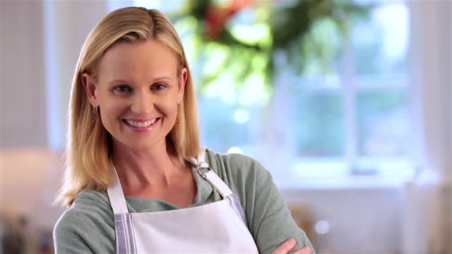 Housewife in apron crosses arms in kitchen, smiles at camera