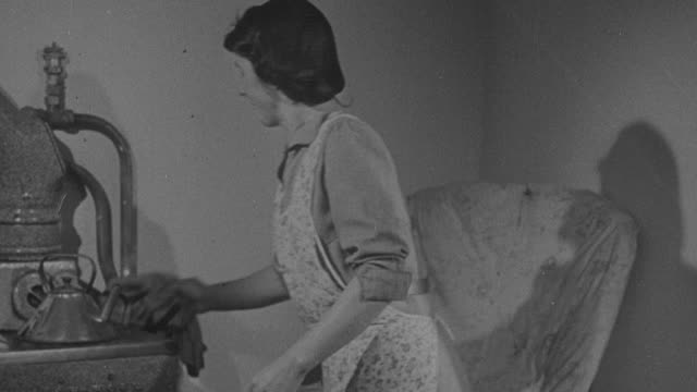 1947 montage housewife in apron plugging in and turning on radio, checking an oven, turning on kitchen faucet to wash dishes, and looking at her child's dirty face / united kingdom - black and white stock videos & royalty-free footage