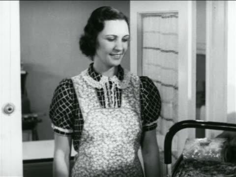 B/W 1938 housewife in apron standing in doorway smiling / industrial