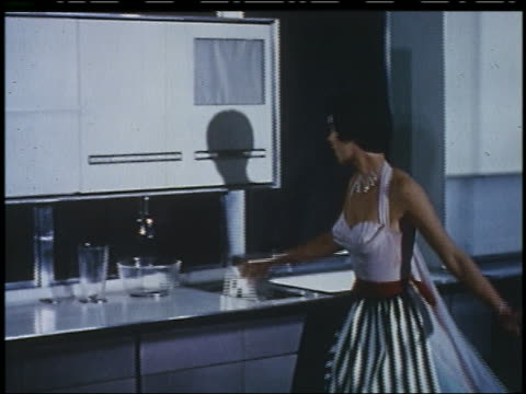 vidéos et rushes de 1956 housewife in formalwear putting card into slot in futuristic kitchen - 1956