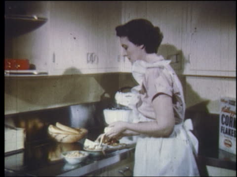 1950 housewife in frilly apron slicing bananas by kitchen sink - hausfrau stock-videos und b-roll-filmmaterial