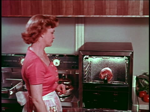 1954 housewife in kitchen activating automatically closing + hiding futuristic oven - ugnsstekt bildbanksvideor och videomaterial från bakom kulisserna