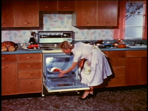 1958 housewife in kitchen putting roast into oven + closing oven - domestic kitchen stock-videos und b-roll-filmmaterial