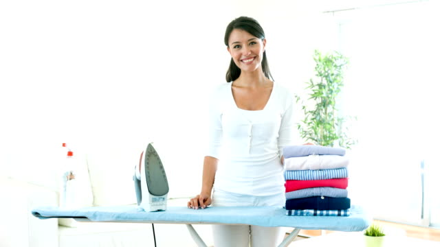 housewife ironing clothes at home - lavori domestici video stock e b–roll