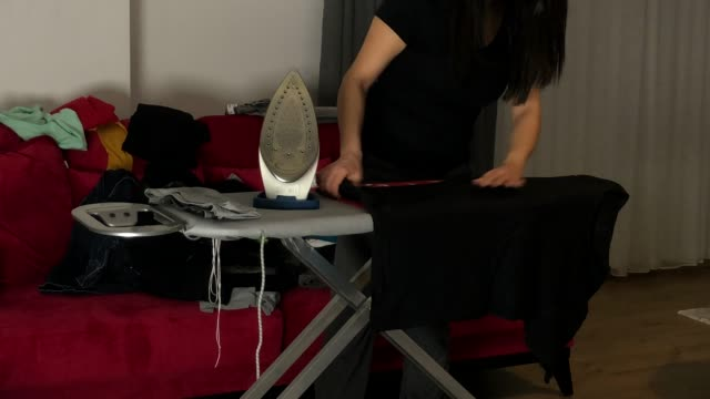 casalinga che stira i vestiti - asse da stiro video stock e b–roll