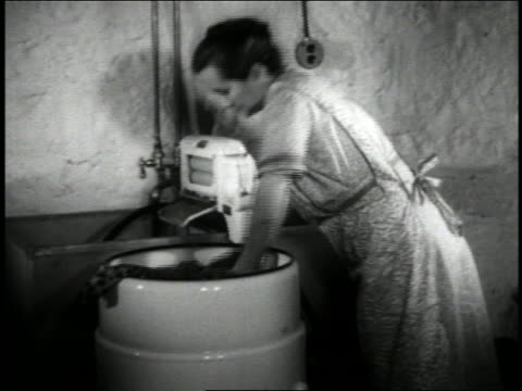 b/w 1940 housewife loading clothing into early washing machine + plugging machine into outlet - stereotypical housewife stock videos & royalty-free footage