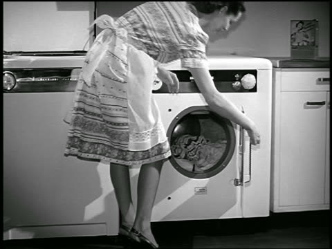 b/w 1948 housewife loading laundry into dryer / industrial - hausfrau stock-videos und b-roll-filmmaterial