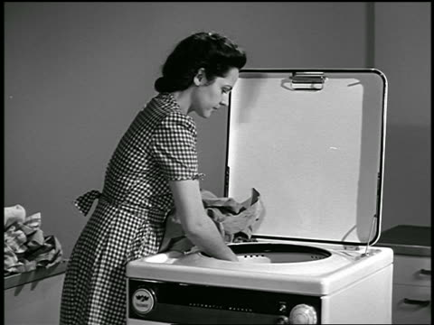 B/W 1947 housewife loading laundry into washing machine / industrial
