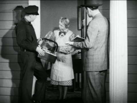 b/w 1938 housewife looking at goods from door-to-door salesman as supervisor takes notes / indus. - doorway stock videos & royalty-free footage