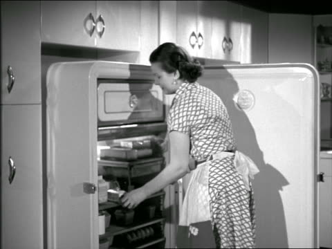 b/w 1950 housewife opening refrigerator checking butter + opening drawer - drawer stock videos and b-roll footage
